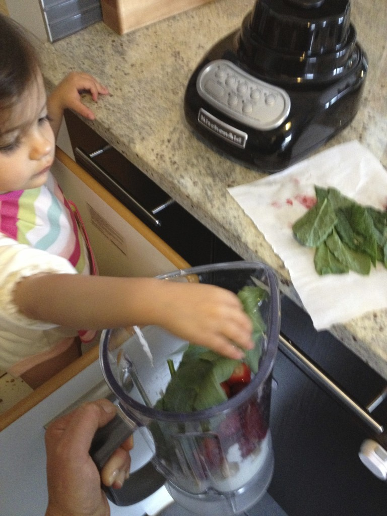 Eliana loves adding ingredients into the blender.