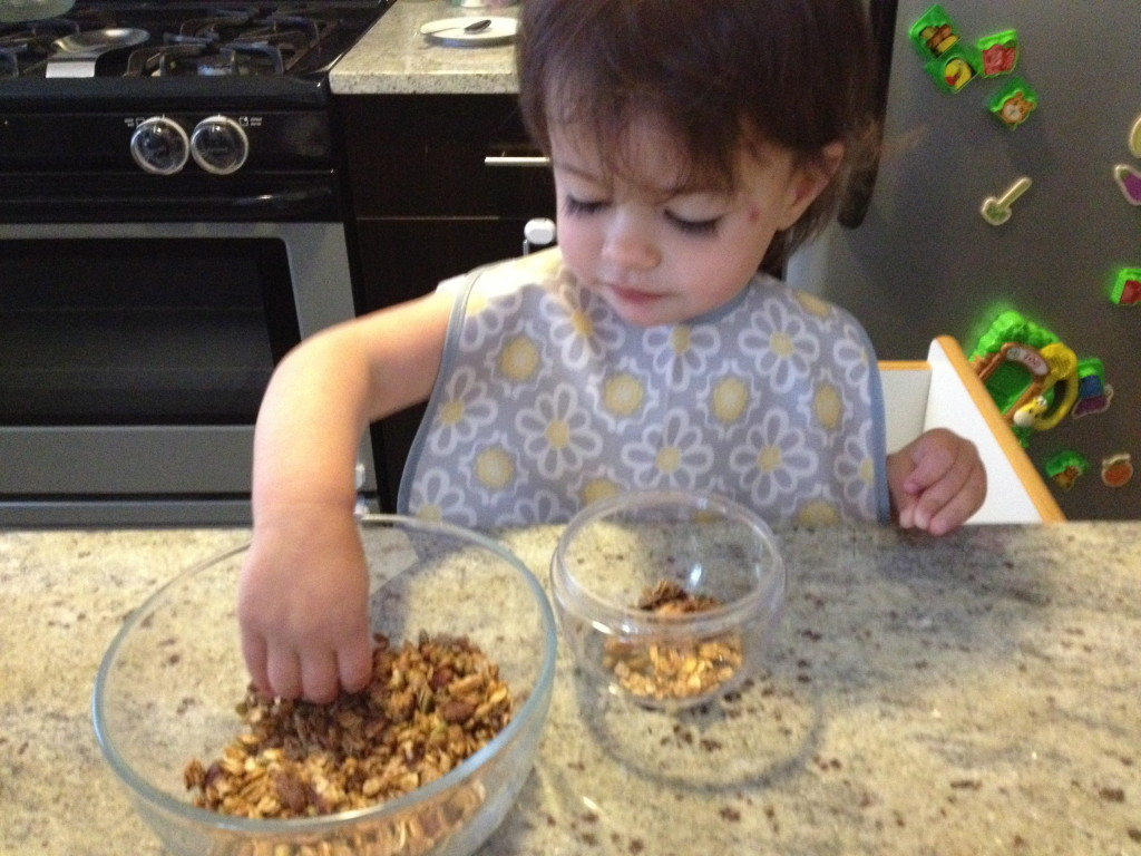 Another morning, Eliana enjoyed adding the granola to her bowl.