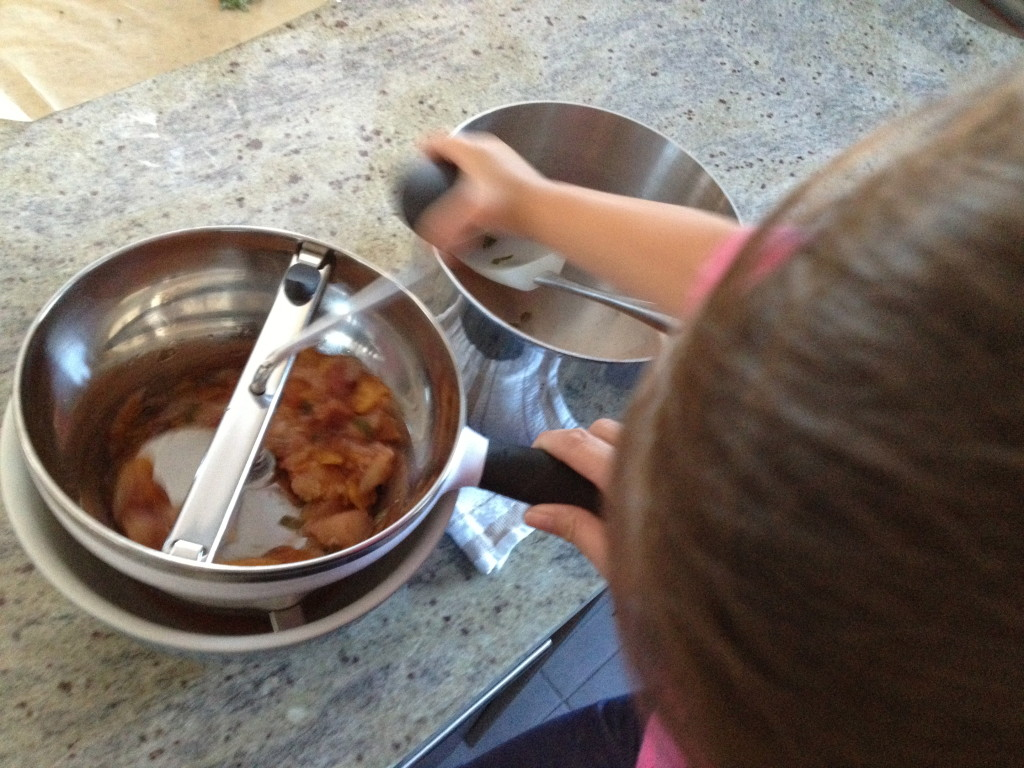 My toddler helping me make puree with my OXO Food Mill.