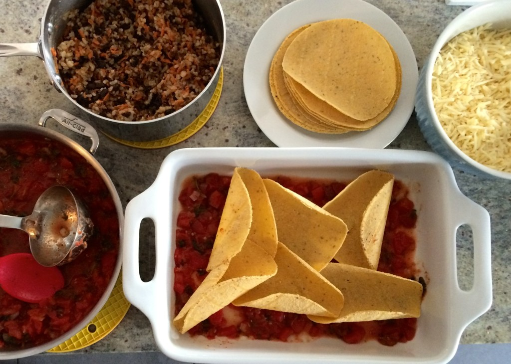 Set up a station with all the components so you can easily build the casserole. Chances are, that unless you stop to take photos along the way while you prep, your tortillas won't curl from the heat of the sauce. But if they do, just flatten them back out with the bean mixture and all will be fine.