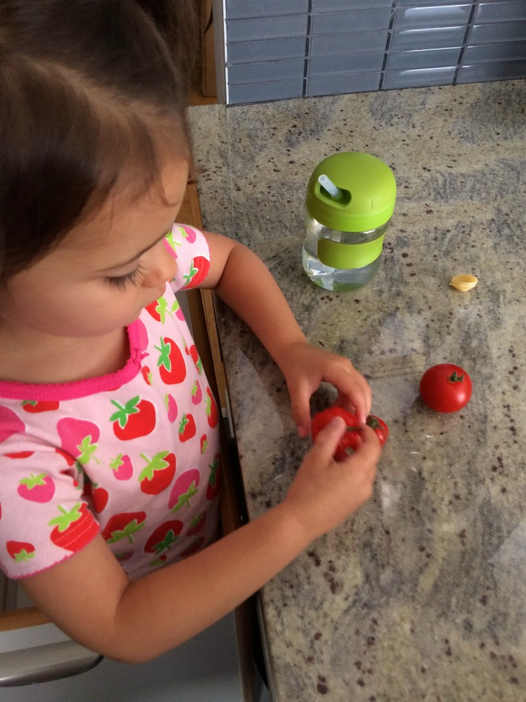 My teeny tiny sous chef pulling off the stems from the tomatoes to make Yellow Squash and Tarragon Purée Pasta from teeny tiny foodie