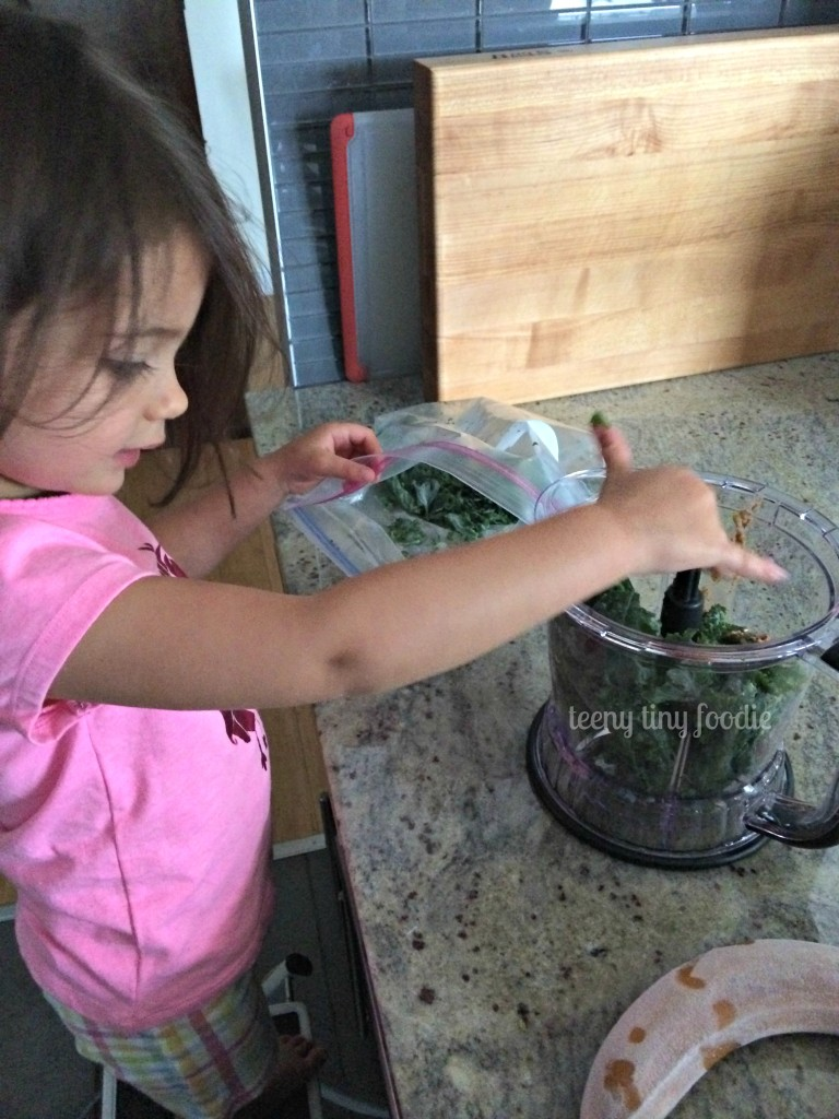 Putting frozen kale in the blender to make a Nutty Green Smoothie from teeny tiny foodie