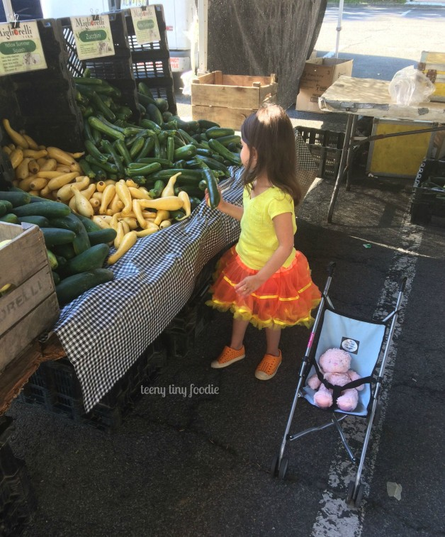 Hmm, which squash should I choose? Eliana is checking out the #MigliorelliFarm booth at #DownToEarthMarkets from #teenytinyfoodie